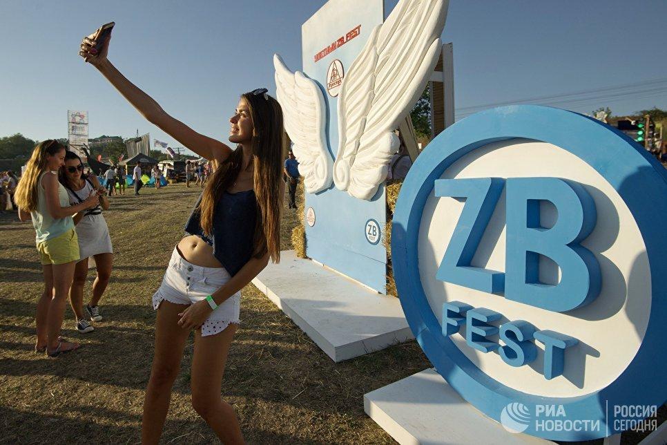 Девушка фотографируется на музыкальном фестивале ZBFest в Балаклаве