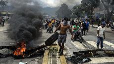 Антиправительственные активисты строят баррикаду в городе Венесуэлы, Валенсия. 6 августа 2017