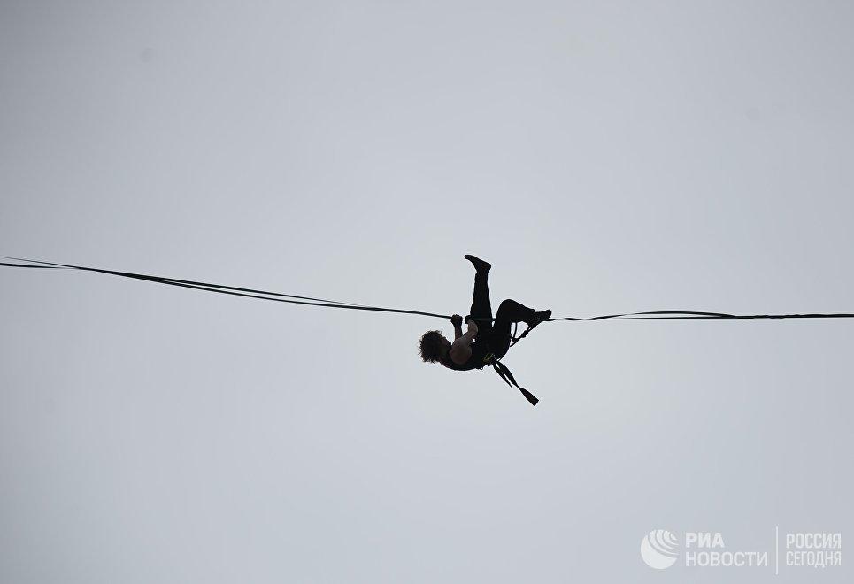 Канатоходец Максим Кагин во время прохода по стропе, натянутой на высоте 126 метров между двумя небоскребами жилого комплекса Чемпион Парк, в Екатеринбурге