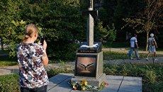Женщина фотографирует памятник украинским военным, погибшим в Донбассе