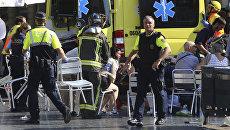 Скорая помощь оказывает помощь пострадавшим на месте наезда микроавтобуса на пешеходов в Барселоне. 17 августа 2017