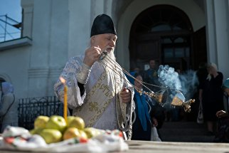 Священнослужитель и верующие во время богослужения в честь праздника Преображения Господня у собора Воздвижения Креста Господня в Омске. 19 августа 2017