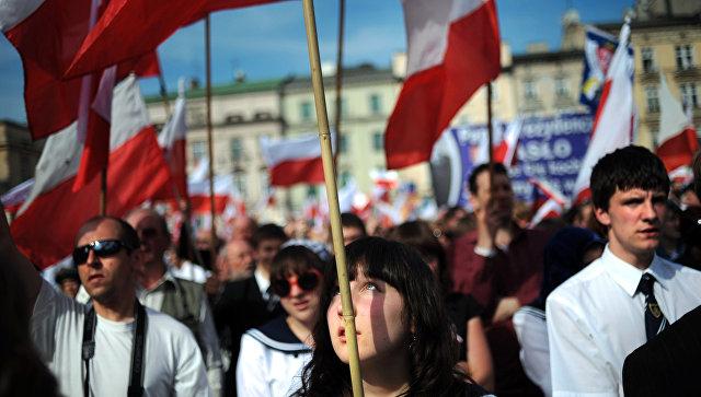 Жители Кракова с польскими флагами на площади города. Архивное фото