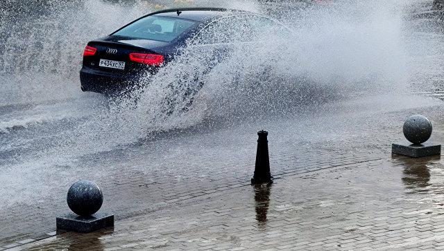 Автомобиль едет по улице Москвы во время дождя. Архивное фото
