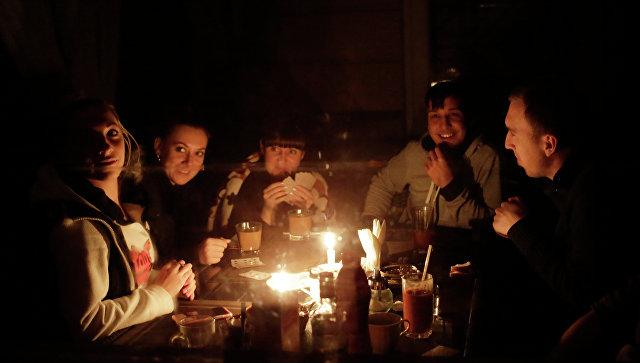 Люди сидят при свечах на кухне в своем доме. Архивное фото
