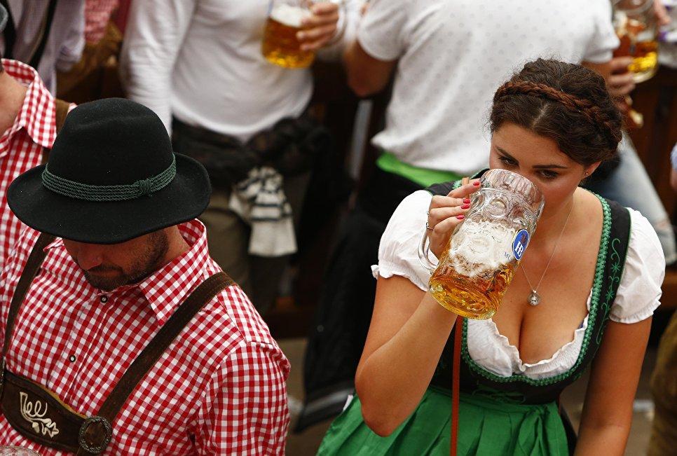 Гостья фестиваля пьет пиво на открытии Октоберфест в Мюнхене