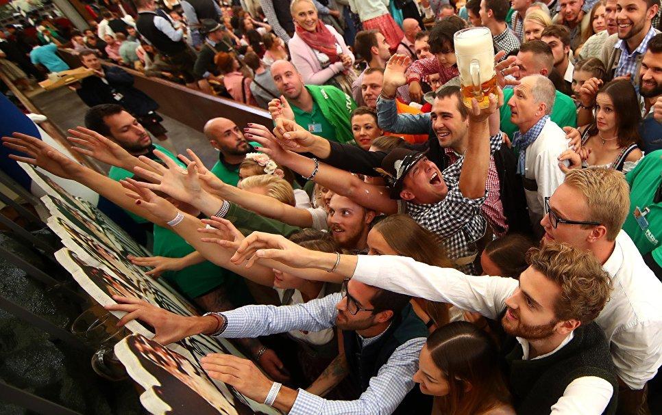 Гости добираются до одной из первых кружек пива на открытии фестиваля Октоберфест в Мюнхене