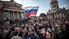 Посетители концерта Песни Победы на площади Жандарменмаркт в центре Берлина