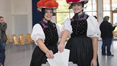 Меолодые немки в традиционной одежде региона называемого Черный лес на избирательном участке в Германии. 24 сентября 2017