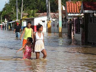 Люди гуляют по улице затопленной в результате разлива реки Юна, вышедшей из берегов после урагана Мария. 24 сентября 2017