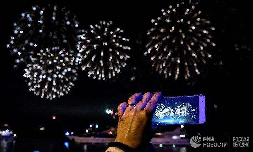 Посетительница фотографирует на мобильный телефон на церемонии закрытия 7-го Московского международного фестиваля Круг Света 2017 на Останкинском пруду в Москве