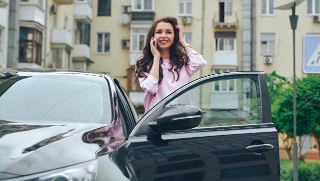 Девушка разговаривает по телефону возле автомобиля