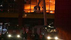 Сотрудники пожарной охраны МЧС РФ во время тушения пожара на строительном рынке Синдика, расположенном у МКАД в районе Строгино. 8 октября 2017