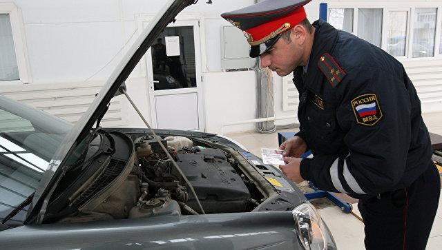 Сотрудник ГИБДД проводит технический осмотр личного автотранспорта. Архивное фото