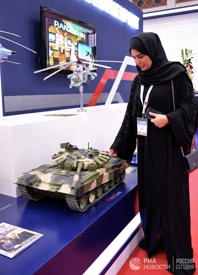 Посетительница рассматривает макет танка Т-90С на стенде компании Рособоронэкспорт на международной оборонной выставке BIDEC-2017 в Бахрейне