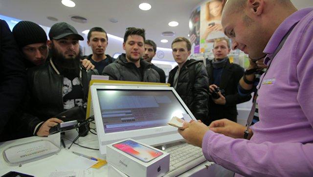 Продавец за прилавком во время старта продаж нового смартфона от Apple. Архивное фото