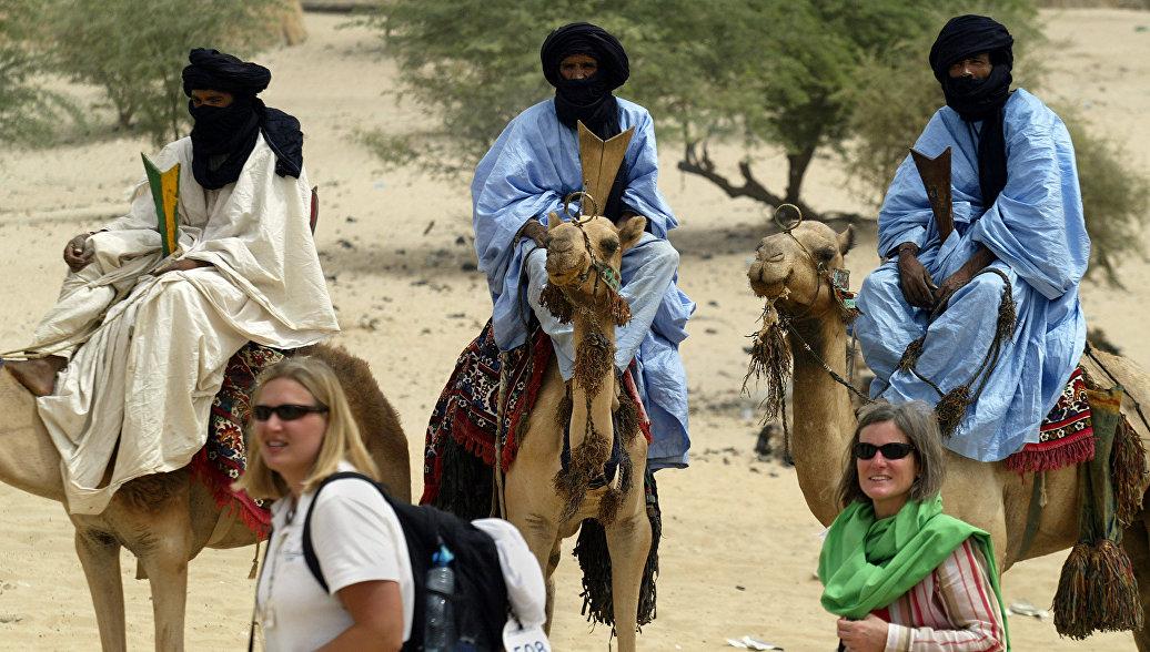 Туристы проходят мимо кочевников в Тимбукту, Мали. Арзивное фото