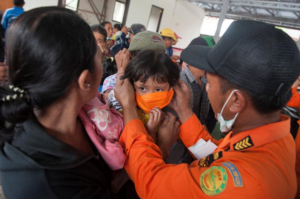 Сотрудник BNPB одевает маску ребенку