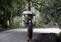Местная жительница носит маску после извержения вулкана Агунг на острове Бали в Индонезии