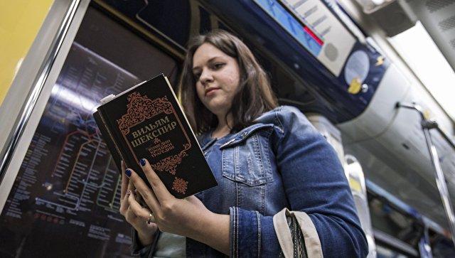 Девушка читает книгу Уильяма Шекспира в поезде московского метро