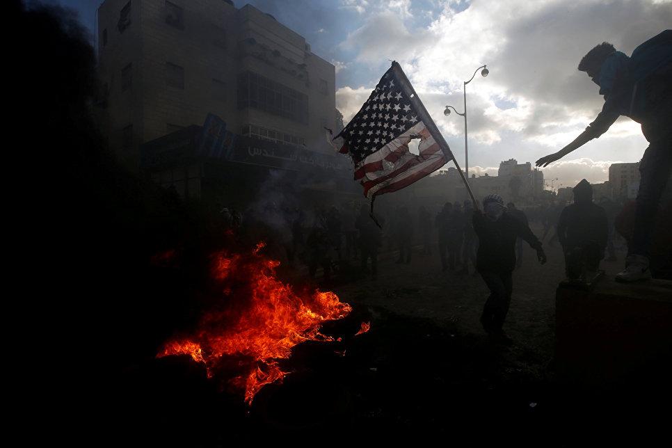 Палестинский протестующий готовится сжечь флаг США во время столкновений с израильскими военными в районе города Рамалла на Западном берегу. 7 декабря 2017 года