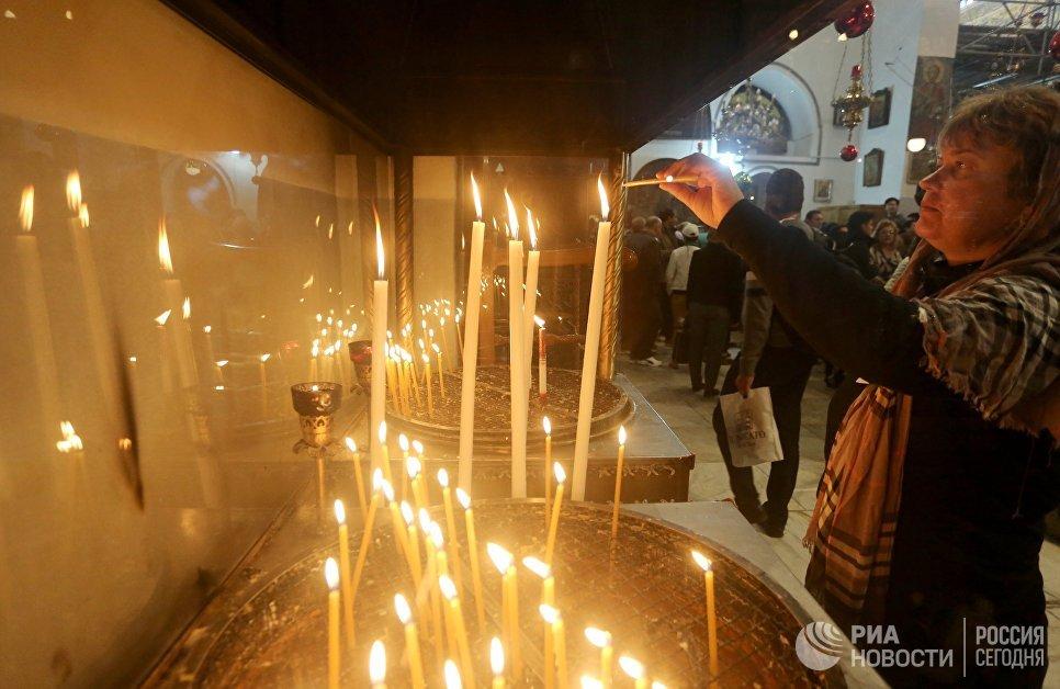 Прихожане в канун Рождества в церкви Рождества Христова в Вифлееме