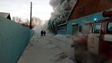 Сотрудники пожарной службы МЧС РФ во время тушения пожара в здании с обувным производством в поселке Чернореченский Искитимского района Новосибирской области. 4 января 2018
