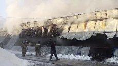 Сотрудники пожарной службы МЧС РФ во время тушения пожара в здании с обувным производством в поселке Чернореченский Искитимского района Новосибирской области. Архивное фото