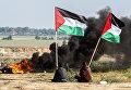 Палестинские демонстранты размахивают своим национальным флагом возле границы между Израилем и Газой. 9 января 2018 год