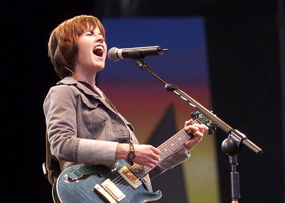 Долорес О'Риордан на сцене с гитарой