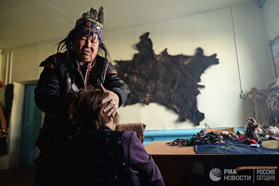 Председатель шаманского общества Адыг-Ээрен (Дух медведя), верховный шаман Республики Тыва Допчун-Оол Кара-оол Тюлюшевич проводит обряд с посетителем в своей комнате в доме, который занимает шаманское общество в Кызыле.