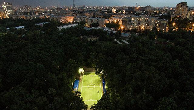 Люди играют в футбол в Нескучном саду в Москве