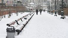 Прохожие в Александровском саду во время снегопада в Москве. Архивное фото