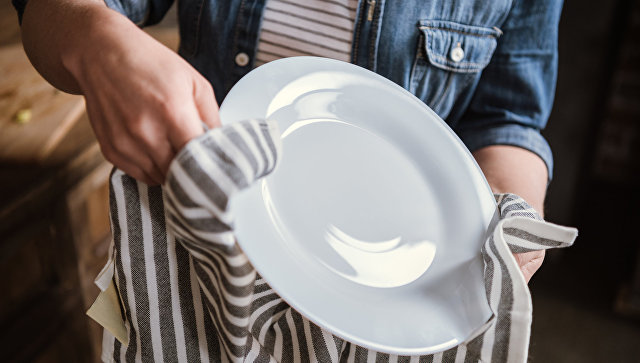 Жінка витирає посуд після миття кухонним рушником.  Архівне фото