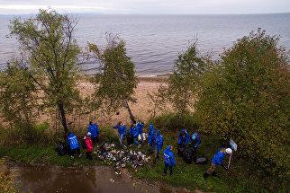 Волонтеры собирают мусор на берегу озера Байкал в районе населенного пункта Мурино во время акции всероссийского волонтерского экологического марафона EN+ Group 360 минут