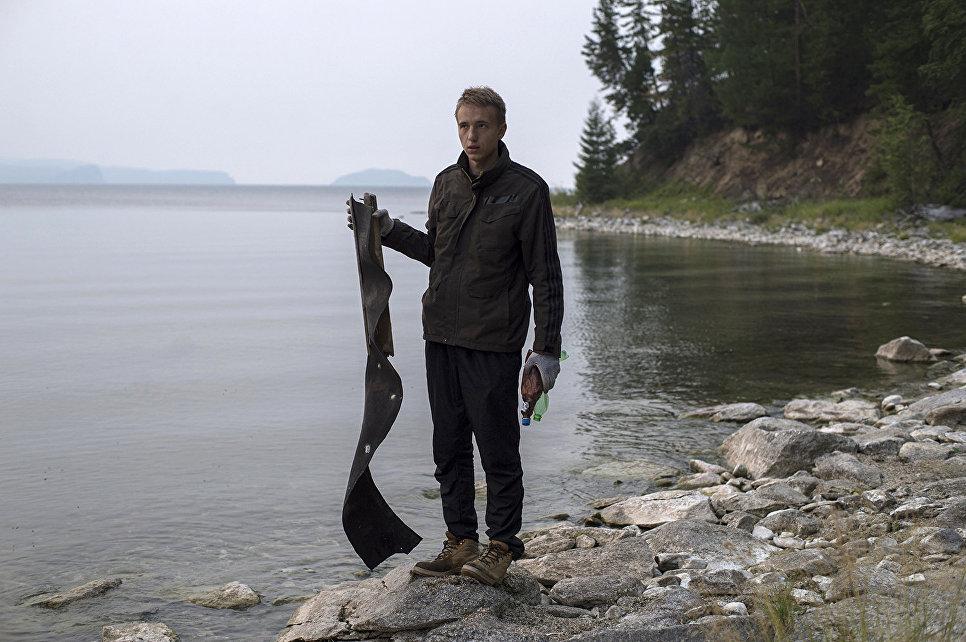 Волонтер Байкальской береговой службы собирает мусор на берегу озера Байкал