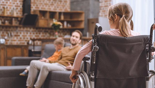 Девочка в инвалидном кресле дома