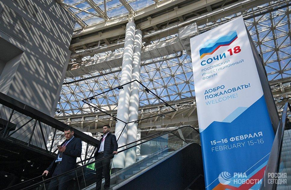 Посетители у баннера Российского инвестиционного форума в Сочи. 14 февраля 2018