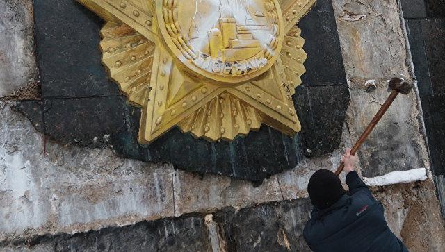 Националист сбивает облицовку на Монументе Славы во Львове. Архивное фото