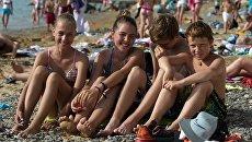 Дети отдыхают на пляже детского оздоровительного лагеря. Архивное фото