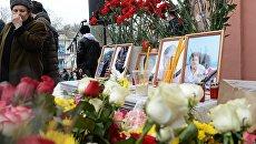 Цветы, свечи и портреты погибших в результате стрельбы у собора Георгия Победоносца в Кизляре во время похорон. 20 февраля 2018