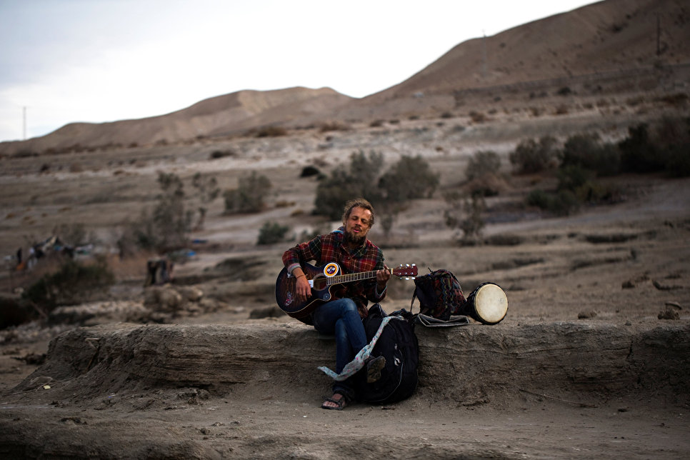 Белорусский турист играет на гитаре на берегу Мертвого моря