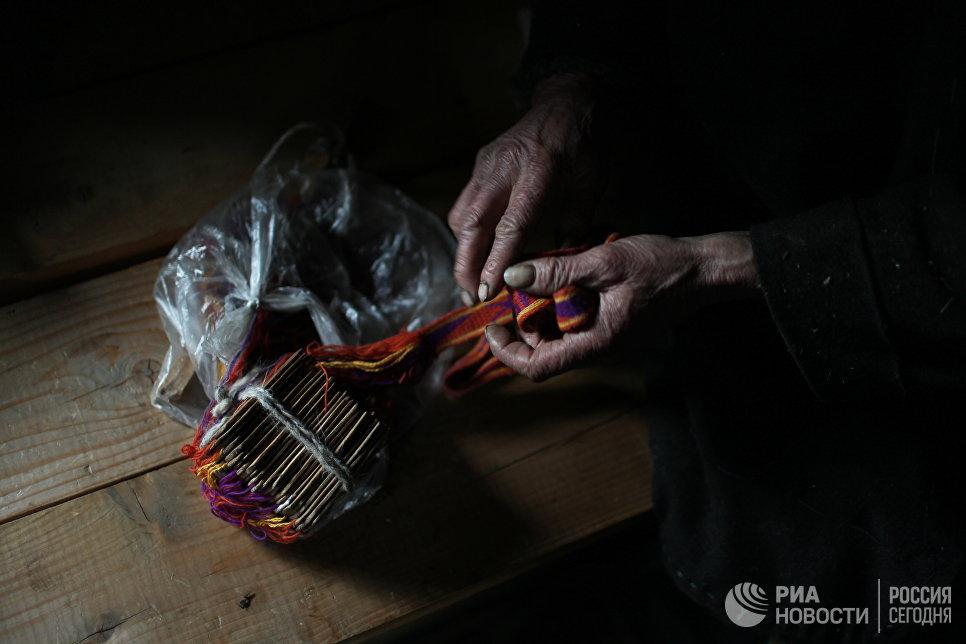 Агафья Лыкова демонстрирует незаконченный именной пояс.