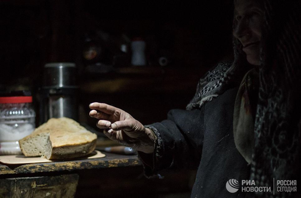 Агафья Лыкова показывает двуперстное крестное знамение.