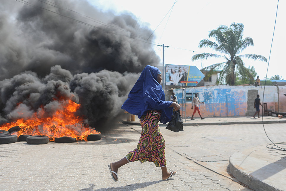 Женщина бежит мимо подожженных шин во время антиправительственной демонстрации в Котону, Бенин