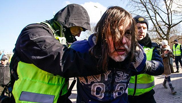 Полицейские задерживают мужчину, протестовавшего против проведения марша бывших латышских легионеров Ваффен СС в Риге. 16 марта 2018