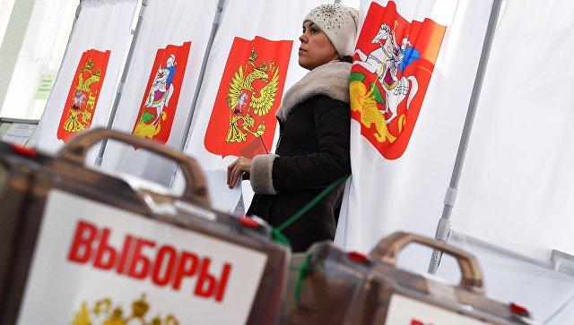 Девушка во время голосования на выборах президента РФ на избирательном участке №13-06 в Москве. 18 марта 2018