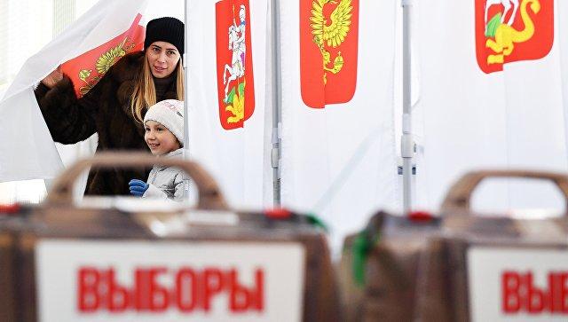 Женщина с ребенком во время голосования на выборах президента РФ на избирательном участке №13-06 в Москве. 18 марта 2018