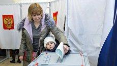 Женщина с ребенком голосует на выборах президента РФ на избирательном участке в Российском центре науки и культуры Кишинева, Молдавия. 18 марта 2018