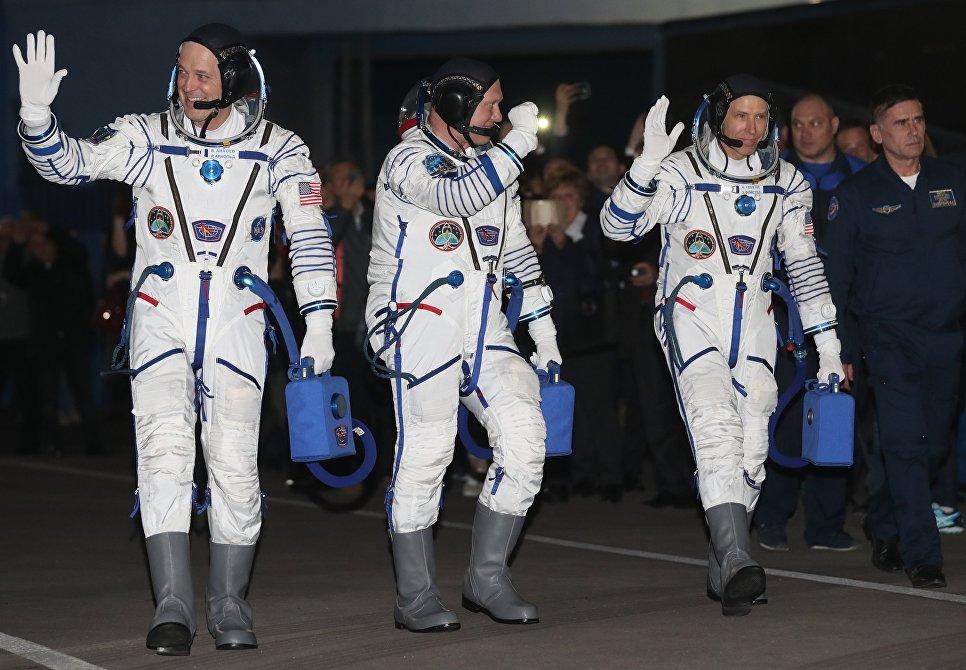 Члены основного экипажа корабля Союз МС-08 экспедиции МКС-55/56 астронавт НАСА Рики Арнольд, космонавт Роскосмоса Олег Артемьев и астронавт НАСА Эндрю Фойстел (слева направо)  перед посадкой в автобус перед отъездом на стартовую площадку космодрома Байконур